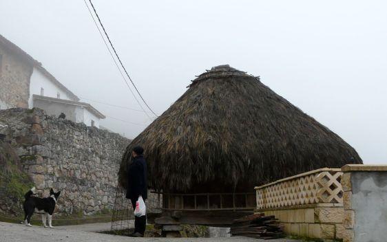 Hórreo em Somiedo, Astúrias, com telhado de palha e estrutura em madeira.